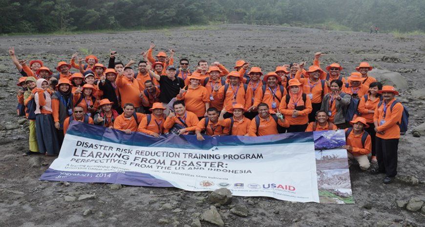 This is a picture of Dr. Karl Kim, Dr. Dolores Foley, and Dr. Bruce Houghton posing with the faculty from Universitas Gadja Mada and Universitas Islam Indonesia and participants from USAID sponsored program on the lava fields in Indonesia