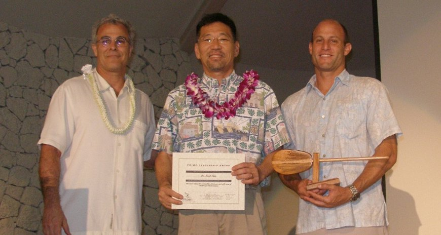 This is a photo of Adam Stein and Jeff Payne presenting an award to Dr. Karl Kim